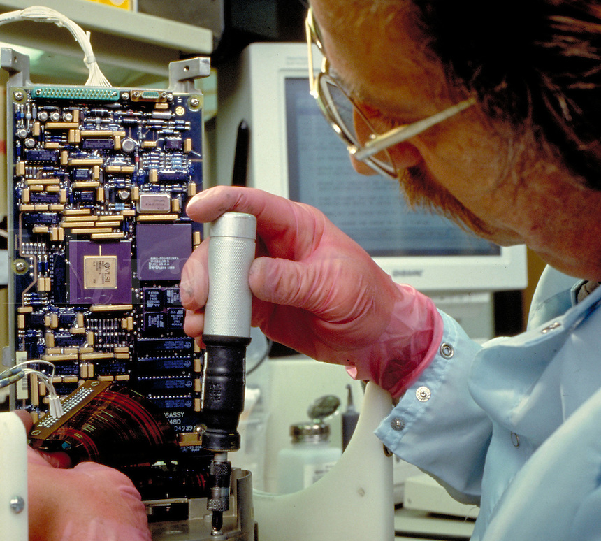 A MAN ASSEMBLES AN ELECTRONIC DEVICE. Defense industry electronics assembly.