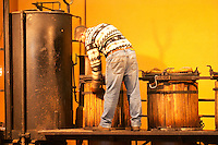 A man putting the lid onto one of the distillation containers. Distillation of marc and fine from wine fermentation residues at M Chapoutier using an old mobile pot still Domaine M Chapoutier, Tain l'Hermitage, Drome Drôme, France Europe