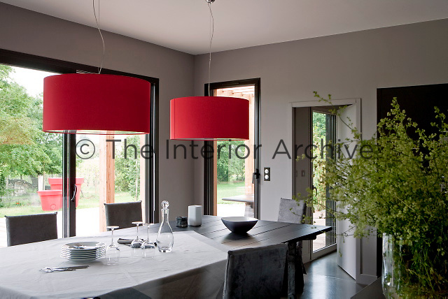 Bright red lampshades above the table in the dining area introduce a splash of colour to this corner of the house