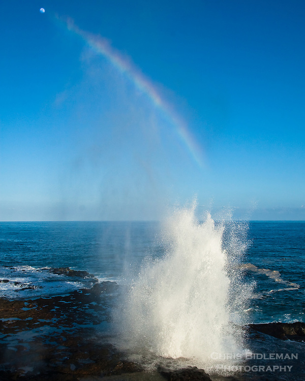 On the south shore of Kauai, Hawaii near the town of Po'ipu, Spouting Horn can be seen squirting water through a blowhole in the small lava shelf caused by the crashing ocean waves.  The moon is being pointed to by the rainbow created by the mist.