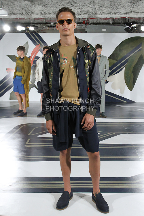 Model Nathaniel poses in a botanical print mesh track jacket in navy, botanical T-shirt in tan, Nylon crew neck in navy, and nylon shorts in navy, from the Perry Ellis Spring 2017 collection by Michael Maccari, on July 11th 2017, during New York Fashion Week Men's Spring Summer 2017.