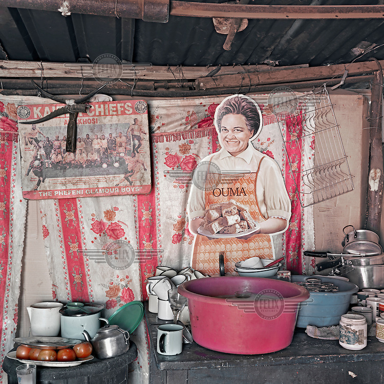 A kitchen clutered with pots, pans and plates and overlooked by an Ouma Rusk cut out figure.