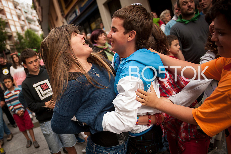 Some boys holding a girl to be beaten by the dancers. Hernani (Basque Country) 26 June 2013. This is part of the traditional 'dance of the fox' in St. Johnn's festival. A group of strong people goes out headed by 'the fox', holding a robe and with cow's bladders in the other hand, surrounding and beating the people they find on the streets (Gari Garaialde/Bostok Photo)
