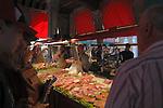 Customers buying from fish vendors at the Rialto market, Venice, Italy. May 2007.