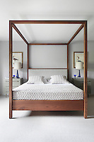 The four-poster bed has been dressed with a knitted bedcover and cushion covers to fit in wth the calm simplicity of the grey tones used throughout the room