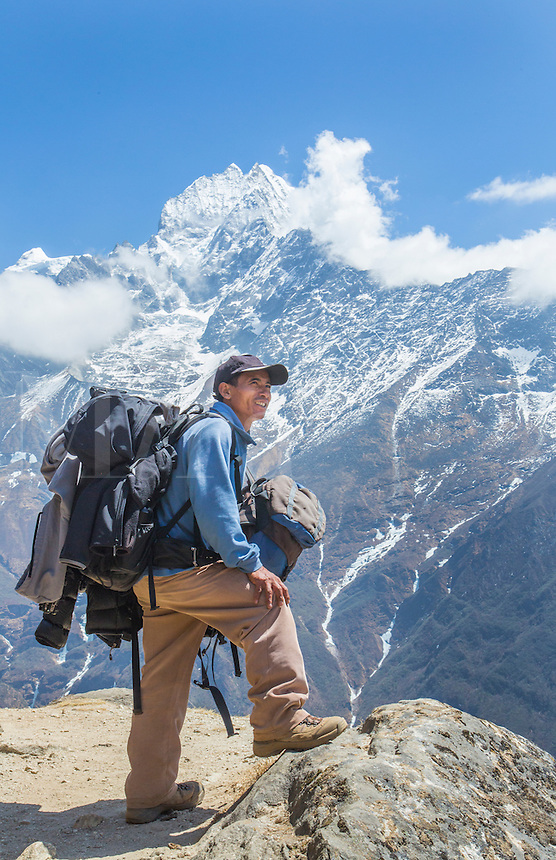 Nepal. Mountain Trekking guide poses with his bags and the Himalayan mountains  in the distance. Solukhumbu, remote, Mt Everest, Himalayas   50