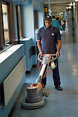 A domestic polishes the floor of a corridor at at Homerton Hospital, Hackney, east London, where threatened industrial action by UNISON members employed by multinational ISS Mediclean in catering, portering and cleaning services lead to a deal which took pay from £4.43 to £5.00 an hour (£5.35 from 1 April 2004),  improved annual leave and the introduction of an occupational sick pay scheme.  The claim was part of the Living Wage campaign carried out in partnership with the East London Citizens Organisation (TELCO).