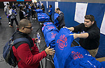 Frank Kreutzer, right, hands out New Student Service Day t-shirts as freshmen and incoming students gather in DePaul's McGrath-Phillips Arena Tuesday, Sept. 5, 2017. Students fanned out across the city to volunteer at dozens of community organizations following the early morning rally on the Lincoln Park Campus. (DePaul University/Jamie Moncrief)