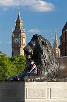 United Kingdom, London: Tourist posing beneath Lion statue in Trafalgar Square with Big Ben in background | Grossbritannien, England, London: asiatischer Tourist posiert fuer ein Erinnerungsfoto an einer Loewenstatue am Trafalgar Square, im Hintergrund der Big Ben