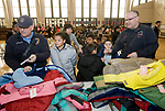 WATERBURY, CT-122117JS03---Waterbury firefighters Lt. Ned Partridge, left, and fire driver Gregg Gyenizs, right, distribute coats to students during a winter coat giveaway Thursday at Bucks Hill School in Waterbury. 300 coats were given away to children from the Waterbury School District with help from the Waterbury Fire Department, and donor support from Cigna, MacDermid, Inc., and Brass Axe Capital and partnership with Operation Warm. <br /> Jim Shannon Republican-American
