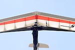 A hang glider pilot flies directly overhead.