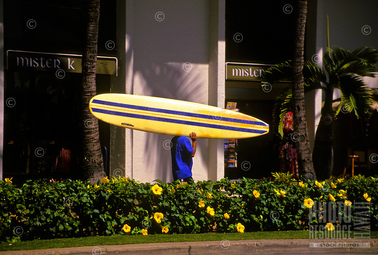 Carrying a surfboard past upscale shops on Kalakaua Ave., Waikiki, Oahu