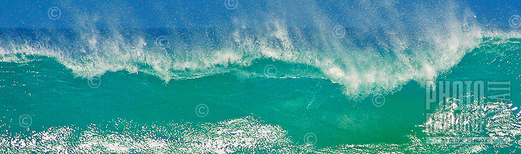 Spray blows backwards from the lip of a turquoise wave as it breaks at Ke'iki beach on the north shore of Oahu.