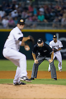 Third base umpire Drew Maher looks on as Charlotte Knights relief pitcher Jarrett Casey (24) delivers a pitch to the plate against the Gwinnett Braves at BB&T Ballpark on August 19, 2014 in Charlotte, North Carolina.  The Braves defeated the Knights 10-5.   (Brian Westerholt/Four Seam Images)