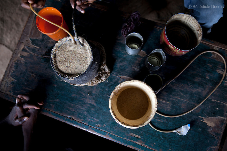 Three Kenyans men drink busaa, a traditional fermented beer, from a common pot using long straws - in a busaa club at midday in a Nairobi slum on March 27, 2013. Busaa is made by crudely fermenting maize, millet, sorghum or molasses. At Kshs 35 per liter it is much cheaper than a Kshs120 half-liter bottle of commercial beer. The local brew was legalised in 2010 and since then busaa clubs have become increasingly popular. Drinking is on the rise in Kenya, especially among young people. Photo: Benedicte Desrus