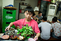 A waiter brings food to a table at Gang Shan Zha Zha, a popular streetside hotpot restaurant on Tiyu Road in central Yuzhong distrist, Chongqing, China.<br /> <br /> The restaurant sits on the site of a former neighborhood garbage collection point and &quot;zha zha&quot; is local slang for &quot;garbage.&quot; The restaurant has been open for 5 years and recently opened a second location elsewhere in Chongqing. A manager of the restaurant said that they server 60-70 tables every night, with many tables' bills coming to over 1000RMB. The restaurant often has a long wait. The site is well-reviewed on online restaurant sites similar to Yelp and is known for having good flavor, serving fresh food, and being clean.