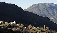 Bubion in its dramatic mountain setting, with mudejar style Church of La Virgen del Rosari, 16th century, gorge of the Poqueira river, Alpujarra, Andalucia, Southern Spain. Moorish influence is seen in the distinctive cubic architecture of the Sierra Nevada's Alpujarra region, reminiscent of Berber architecture in Morocco's Atlas Mountains. Photograph by Manuel Cohen.
