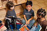Education preschool 3-4 year olds start of day separation sad boy sitting between two girls on rug sad crying horizontal girls noticing his distress and trying to comfort him empathy horizontal