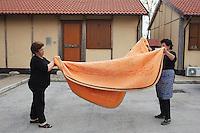 Bonefro: due signore abitanti del villaggio ripiegano una coperta