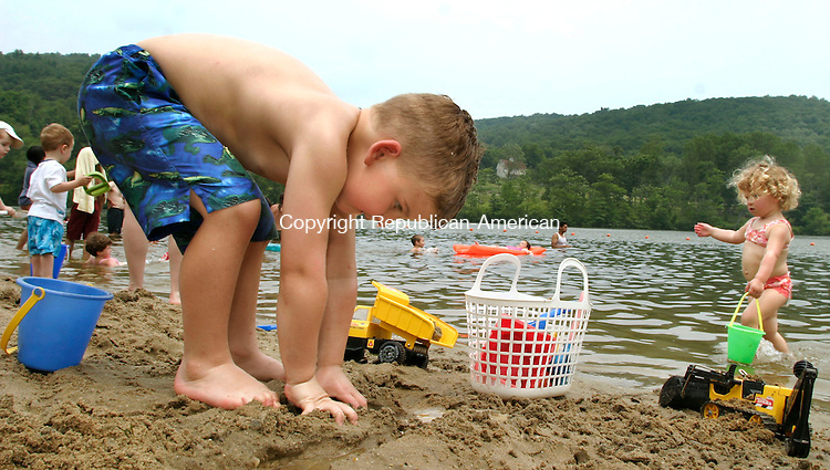 NEW PRESTON, CT--02 JULY 2006 -070206JS03-Teddy Dokla, 4, of Brookfield, makes more mud for his sand castle while his sister Natalia, 2, right, hauls in a pail of water during a visit Sunday to Lake Waramaug State Park in New Preston with their family. -- Jim Shannon Republican-American