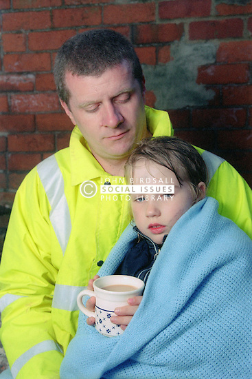 Young girl wrapped in blanket being comforted by worker from emergency services,