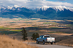 A pickup truck in the National Bison range in Montana with the Mission Mountains across the valley