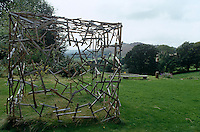 A large wooden sculpture called The Cube by Henry Brudenell-Bruce in the garden