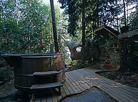"A wood encased hot tub on a deck overlooking the ""accordion"" turtle-like cedarwood-clad house and the surrounding forest"