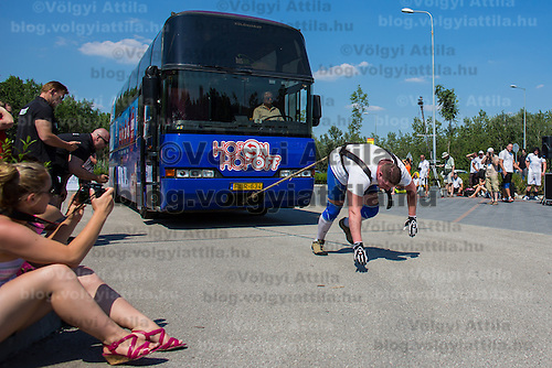 James Rude of USA competes in bus pulling during the Giants Live Strongman Competition in Budapest, Hungary on June 17, 2012. ATTILA VOLGYI
