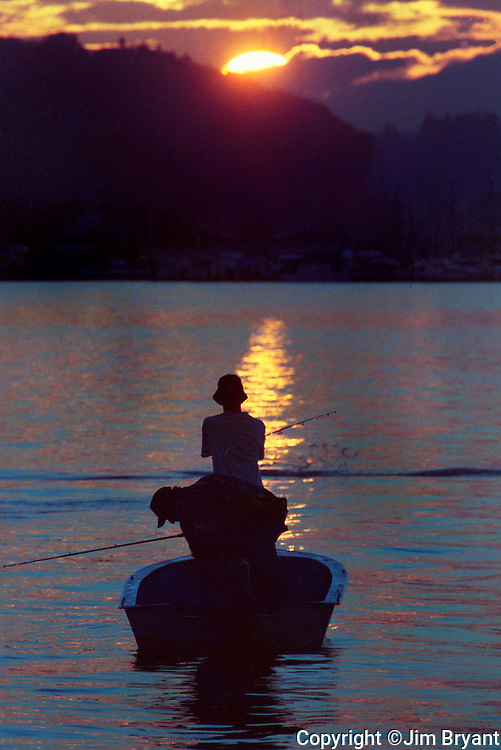 Boat fishermen, fishing for salmon are silhouetted by the setting sun on Sinclair's Inlet near Port Orchard, WA. Jim Bryant Photo