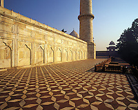Early morning on the raised terrace of the Taj Mahal with beautiful tiled floor and carved marble wall; a cleaner makes his rounds before the crowds arrive; Agra, Indi