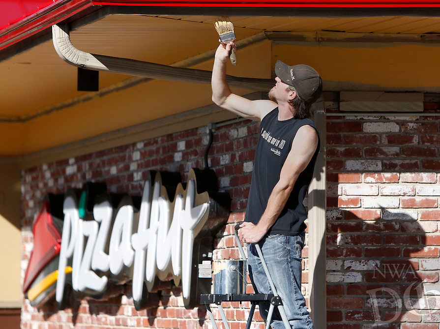 NWA Media/DAVID GOTTSCHALK - 10/15/14 - Justin Batson, with Award Handyman Service of Conway, applies an exterior coat of paint on the Pizza Hut on Archibald Yell Boulevard in Fayetteville Wednesday October 15, 2014. The handyman service is installing new carpet, painting the interior and painting the exterior.