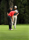 Former United States President Bill Clinton (red shirt) putts as U.S. President Barack Obama (white hat) and Obama's Chief of Staff William Daley (black hat) watch on the first hole during of golf at Joint Base Andrews, Maryland, September 24, 2011. .Credit: Chris Kleponis / Pool via CNP
