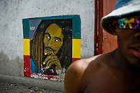 Bob Marley's portrait painted on the wall in the slum of Cité Soleil, Port-au-Prince, Haiti, 24 July 2008. Cité Soleil is considered one of the worst slums in the Americas, most of its 300.000 residents live in extreme poverty. Children and single mothers predominate in the population. Social and living conditions in the slum are a human tragedy. There is no running water, no sewers and no electricity. Public services virtually do not exist - there are no stores, no hospitals or schools, no urban infrastructure. In spite of this fact, a rent must be payed even in all shacks made from rusty metal sheets. Infectious diseases are widely spread as garbage disposal does not exist in Cité Soleil. Violence is common, armed gangs operate throughout the slum.