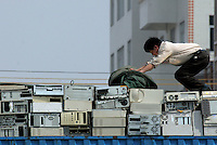 A worker unpacks a truck-load of e-waste which has just arrived in Guiyu in Guangdong province.