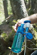 A hiker uses a water filtering system on Meader Ridge Trail during the spring months.  Located in the White Mountains, New Hampshire USA. .Note:
