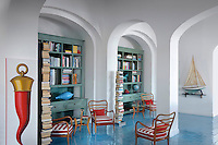 Tolomeo columns of books complement the blue-washed more traditional bookshelves in the reading room