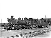 Engineer side view of D&amp;RGW #486 K-36 in Alamosa with roundhouse in background and dual track in foreground.<br /> D&amp;RGW  Alamosa, CO  7/4/1938