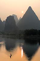 A man paddles a bamboo raft on the Lijiang River under the rising sun and karst mountains, Yangshuo, Guanxi, China