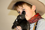 A young cowboy holding a black bunny rabbit Focus on the bunny