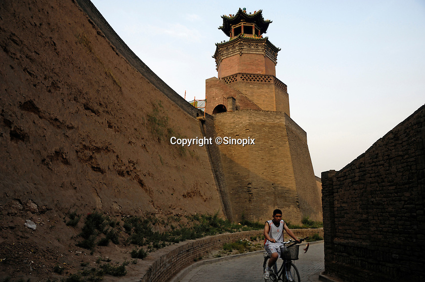 A man cycles within Pingyao Ancient City in  Shanxi, China. Being one of the four wholly-protected ancient cities in China, Pingyao Ancient City is thought of as the 'treasure house' of ancient Chinese architectures..05 Jun 2007.