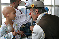 """Cris L'ariste an Israeli  medical clown who works in Hadassah and he is a member of a group call """"Dream Doctor"""", plays with Anwar Ibrahim, 3, from the Arab Israeli town of Abu Gosh, at the Oncology Day Care unit at Hadassah Ein Karem hospital. Photo by Quique Kierszenbaum."""