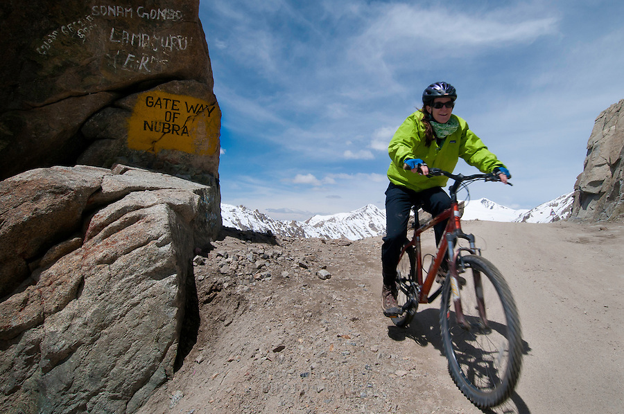 "Mountain biking past the ""Gateway of Nubra"", on the highest motorable road in the world,  Himalayan Mountains, Ladakh, India."