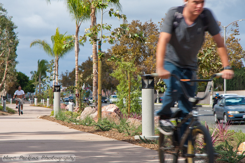 Two bicyclists ride down the Harbor Boulevard Cornerstone Bike Trail in Costa Mesa, California.