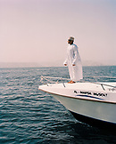 OMAN, Muscat, man standing on deck of boat in traditional clothing at sea