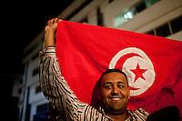 23 ottobre 2011 Tunisi, elezioni libere per l'Assemblea Costituente, le prime della Primavera araba: un uomo sventola la bandiera tunisina sorridendo.<br /> premieres elections libres en Tunisie octobre <br /> tunisian elections october Festeggiamenti vittoria Ennhada