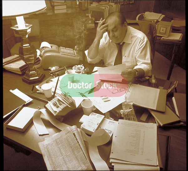 man surrounded by paperwork and adding machine