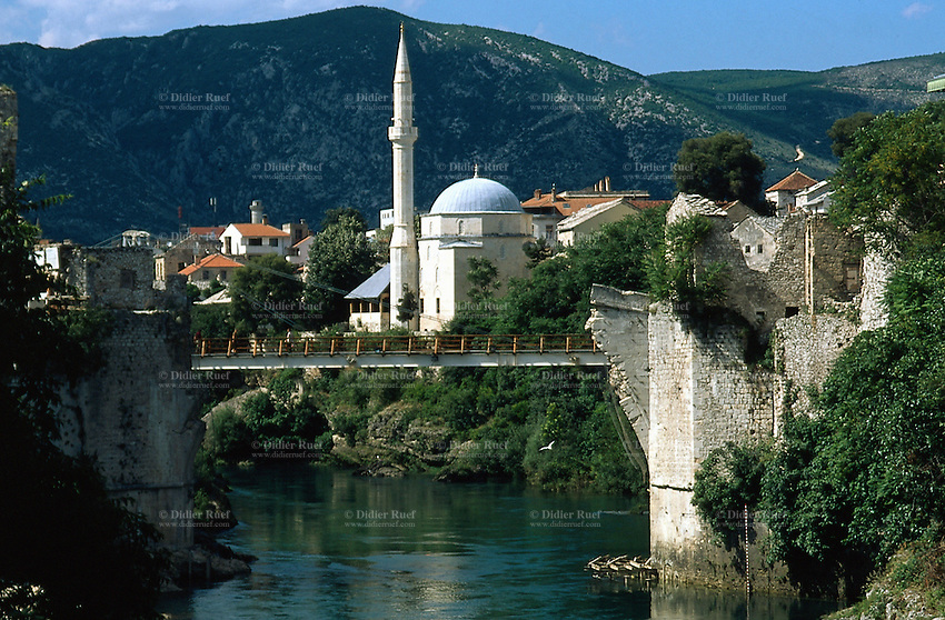 Bosnia. Mostar. A view on the remains of the famous 15th century turkish bridge over the Neretva river. The old bridge was shelled and destroyed in 1993 by croat bombs during the bosnian war (croats against muslims). The bridge's destruction was an attack on a symbol of history, resistance and of Mostar's union between religions. A footbridge was built as an overpass to allow people to get on the other side of the city. 4.06.02  © 2002 Didier Ruef