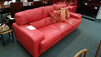 Pictured: One of the red leather settees at the British Heart Foundation charity shop in Swansea, Wales, UK. Wednesday 12 April 2017<br /> Re: A mystery Swansea woman has donated £16,000 worth of furniture to a charity shop.<br /> The British Heart Foundation shop in Kingsway in Swansea has benefitted from the haul.<br /> Some of the furniture is so new, that similar items are still for sale with the original retailer; Furniture Village.<br /> The haul includes a side board, a display cabinet, two two-seater sofas, a three seater sofa and dining table complete with six chairs.<br /> The dining table is listed online with Furniture Village for £1,865, the display cabinet for £1,865, and a pair of the six dining chairs for £1065.<br /> The British Heart Foundation will be selling the items for probably around a quarter of the original value.