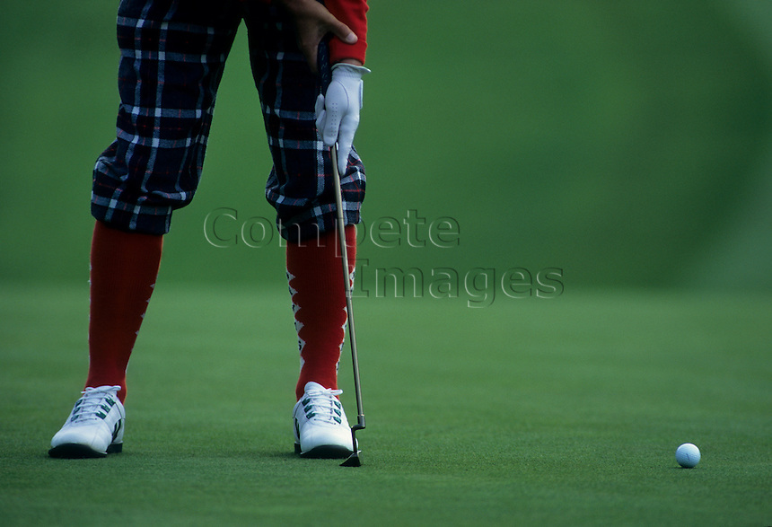 Golfer in plus fours putting a shot